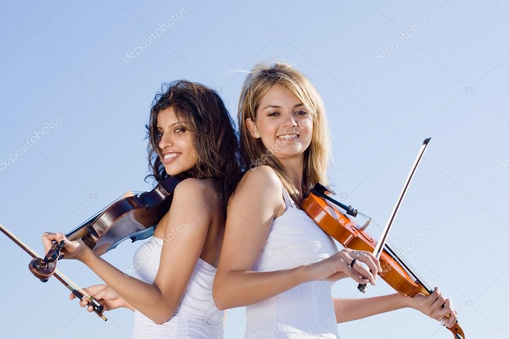 Two young female violinist with violins outdoors