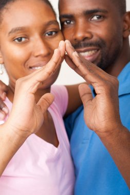 African american couple using hands forming home concept