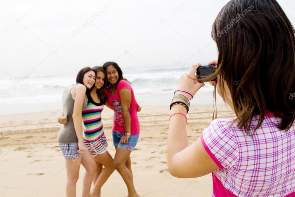 Group of teen girls taking photos on beach
