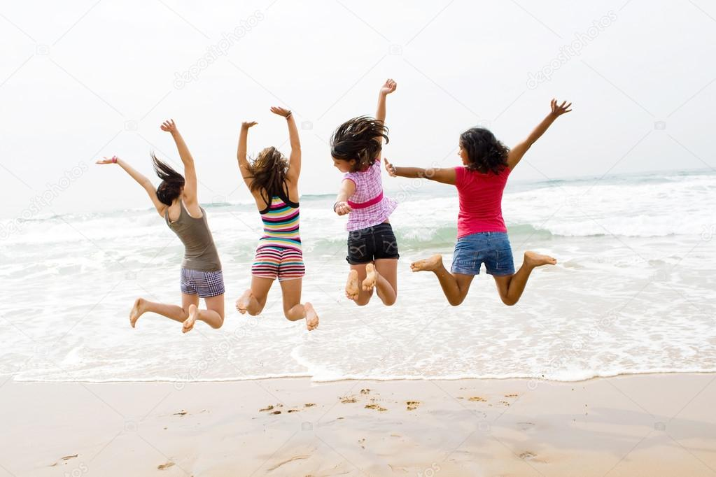 Group of teen girls jumping on beach
