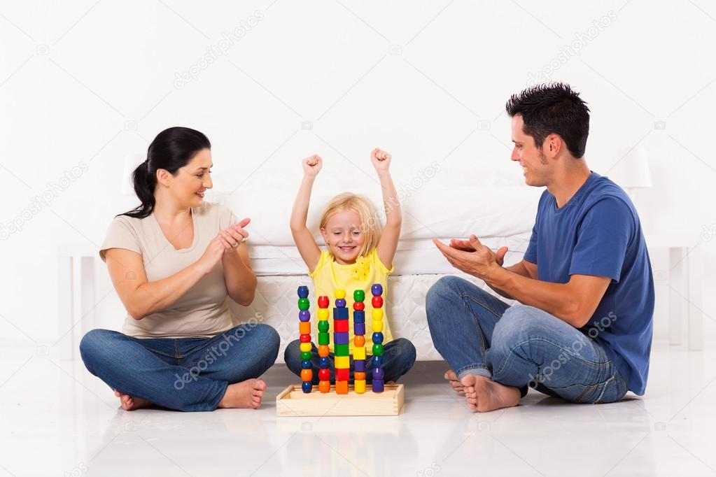 Happy Little Girl Playing Toys With Parents On Bedroom Floor U2014 Stock Photo