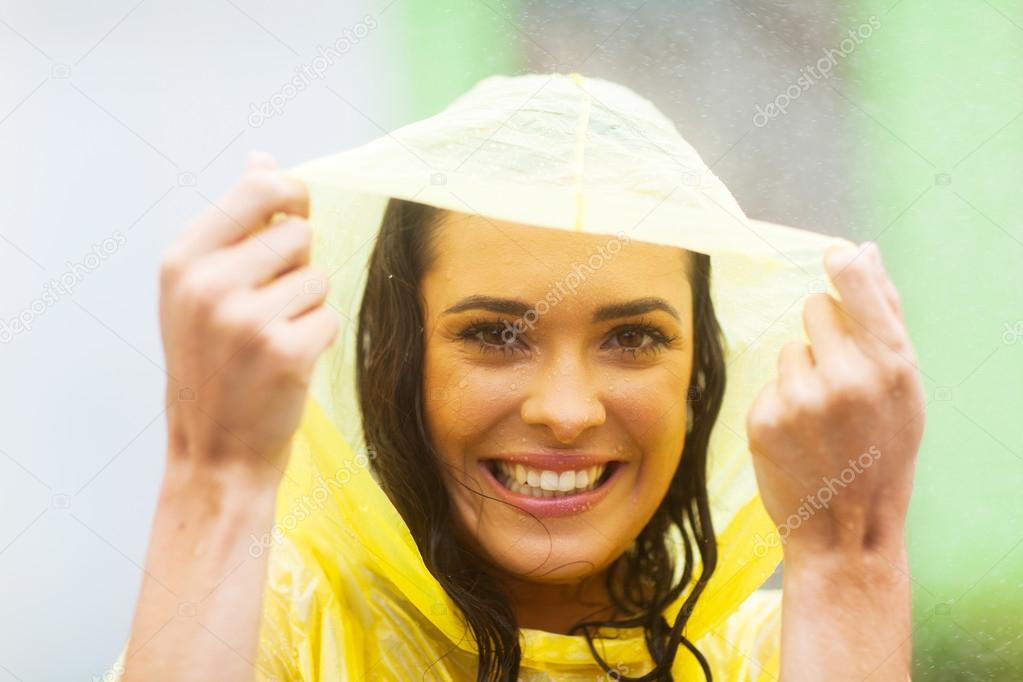 Happy young woman in poncho in the rain