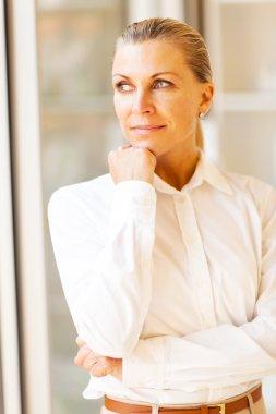 Thoughtful female senior office worker looking outside window