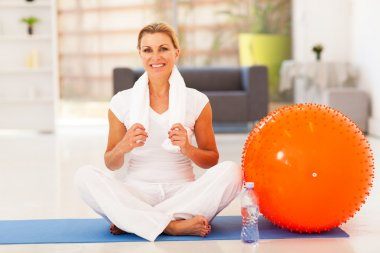 Mature woman resting on exercise mat after fitness workout