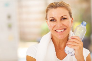 Healthy senior woman with exercise towel and water