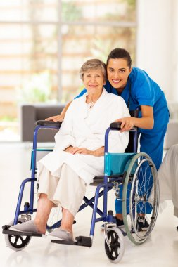 Elderly woman and young caregiver at home