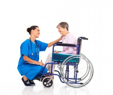Friendly nurse talking to disabled senior patient