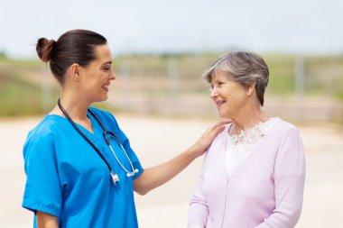 Happy young nurse talking to senior woman outdoors