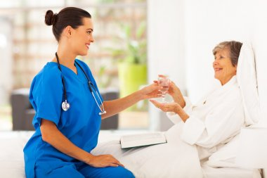 Caring young caregiver bring a glass of water to senior woman on bed