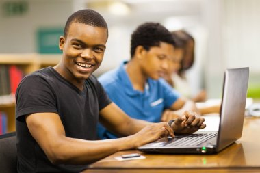 Happy male african college student using laptop in library