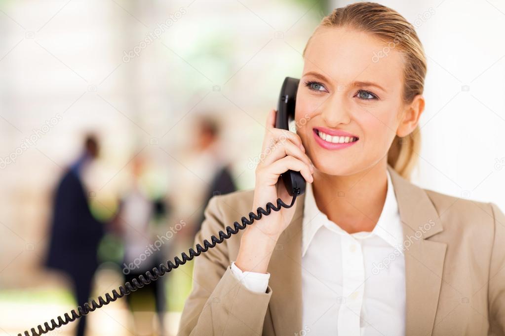 Happy female office worker talking on landline phone