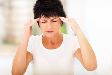Woman having headache and massaging forehead