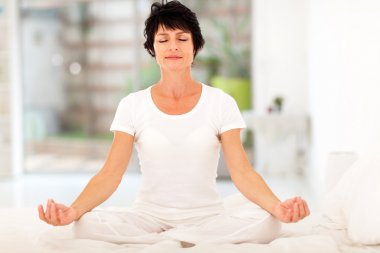 Woman meditation on bed at home