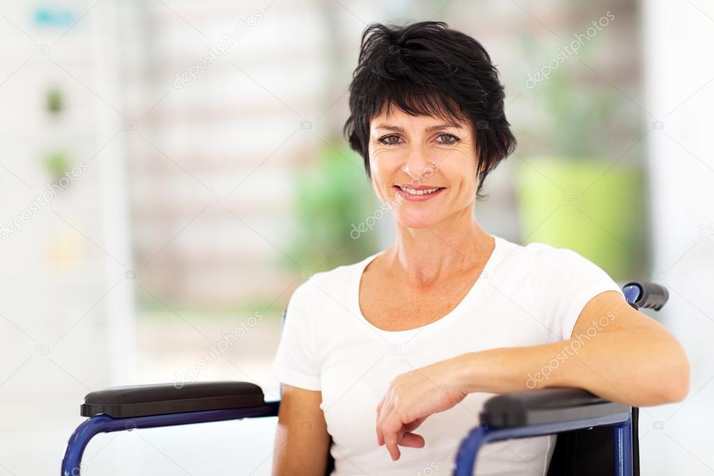 Optimistic handicapped middle aged woman sitting on wheelchair