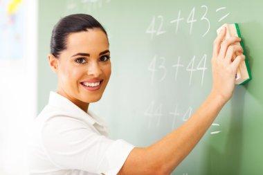 Beautiful female elementary school teacher erasing chalkboard