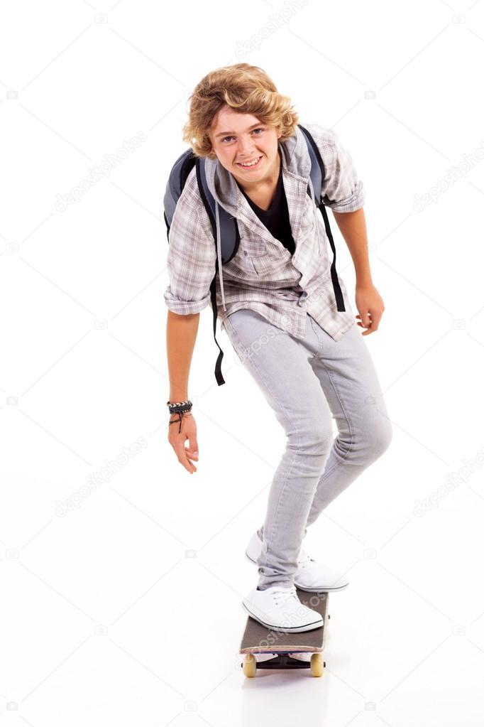 Teen boy skateboarding isolated on white