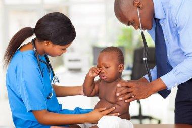 afro american pediatrician and nurse examining a baby boy