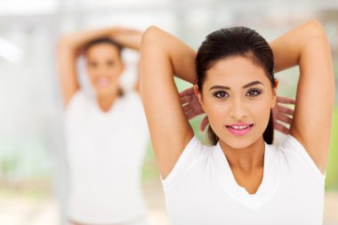 Woman exercising with hands back on her head