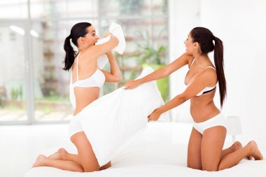 two girl friends having pillow fight