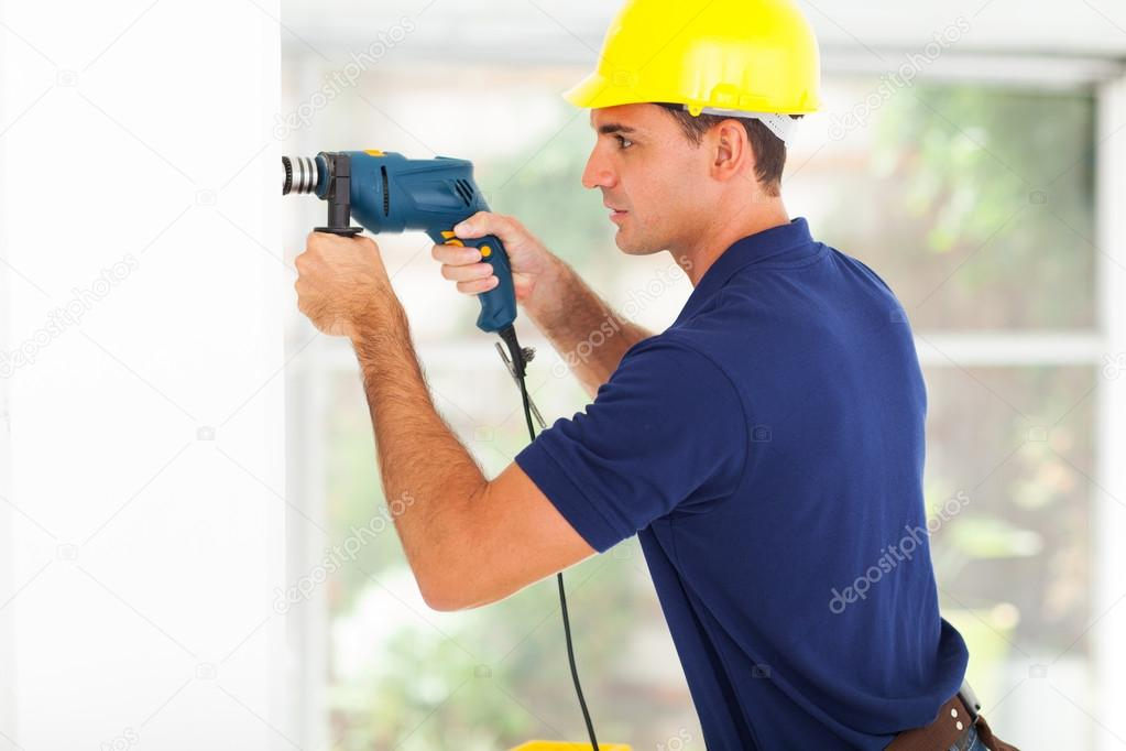 Young builder drilling holes on the wall