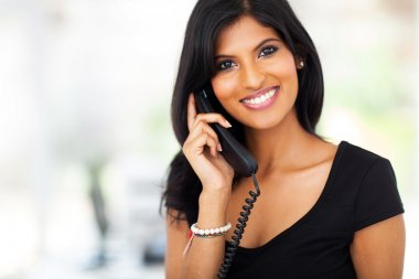 Gorgeous young businesswoman answering telephone in office stock vector