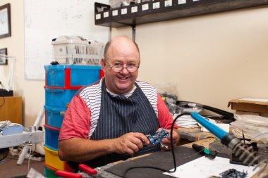 happy senior man in workshop