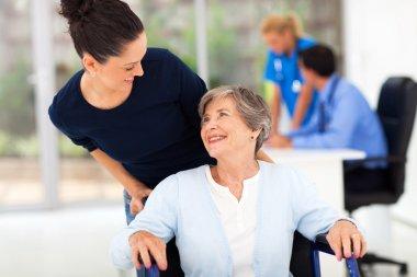 daughter accompanying senior mother to visit doctor