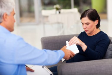 therapist handing tissue to an upset middle aged patient