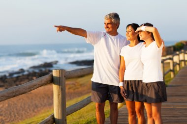 middle aged man pointing at ocean with family