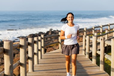 fit mid age woman jogging at the beach
