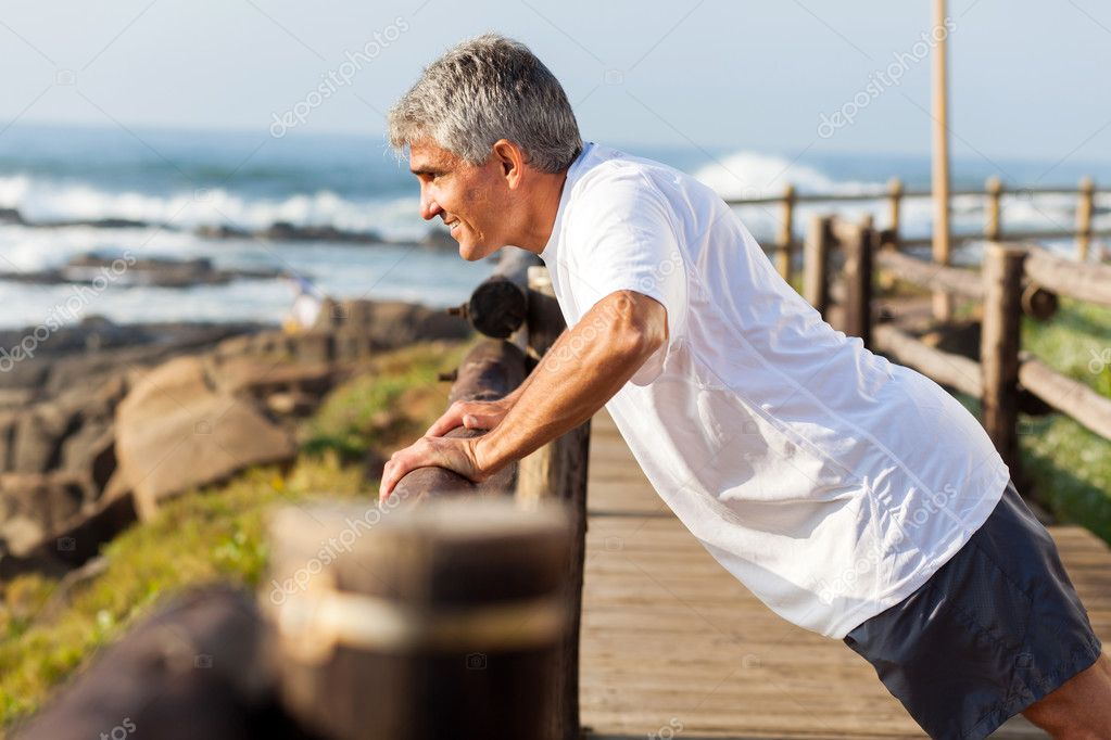 fit senior man exercising at the beach