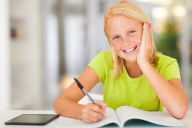 happy teen schoolgirl doing homework