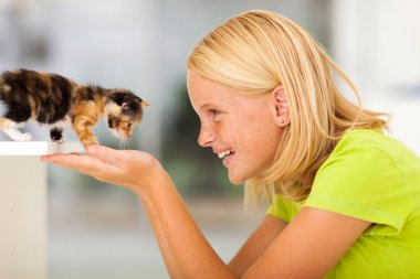 loving teen girl playing with pet kitten