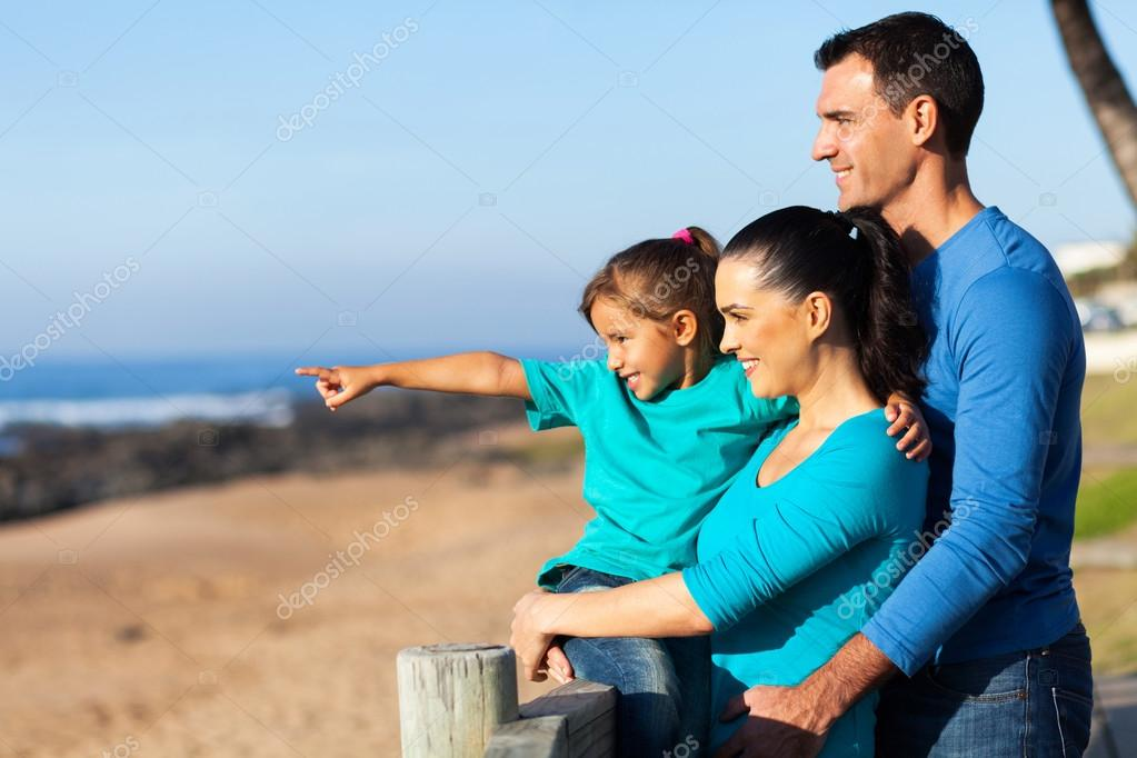 little girl pointing at ocean with parents