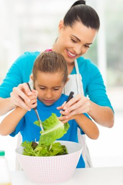 loving mother teaching daughter mixing salad
