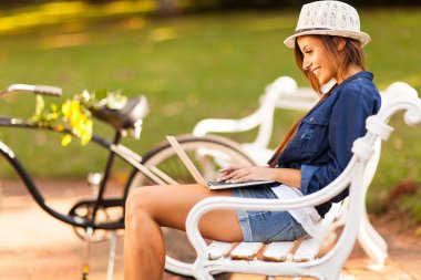 young woman at the park using laptop