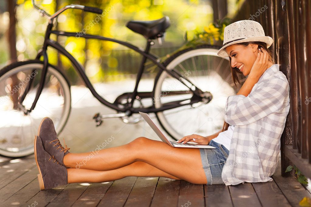 young woman browsing internet on her laptop outdoors