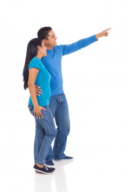 indian couple pointing at empty copy space