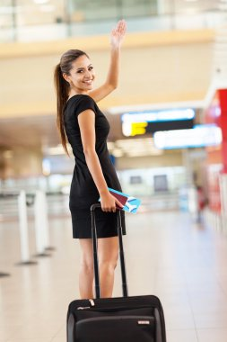 businesswoman waving goodbye at airport