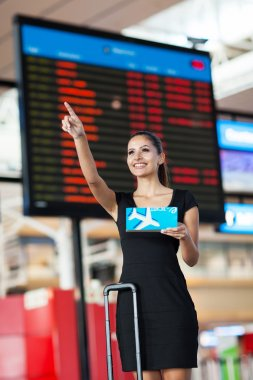 Cheerful businesswoman at airport pointing in front of flight information board stock vector