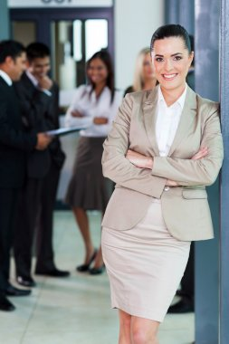 businesswoman standing in office with colleagues on background