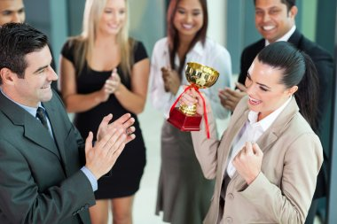 Cheerful female corporate worker receiving a trophy