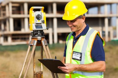 mid age land surveyor working at construction site