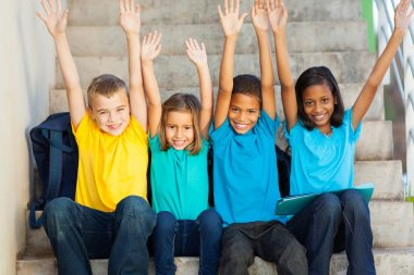 happy primary students with hands raised