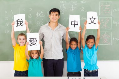 Friendly male chinese teacher with group multiracial primary students holding papers saying i love chinese stock vector