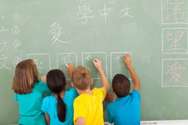 rear view of students learning chinese writing on chalkboard