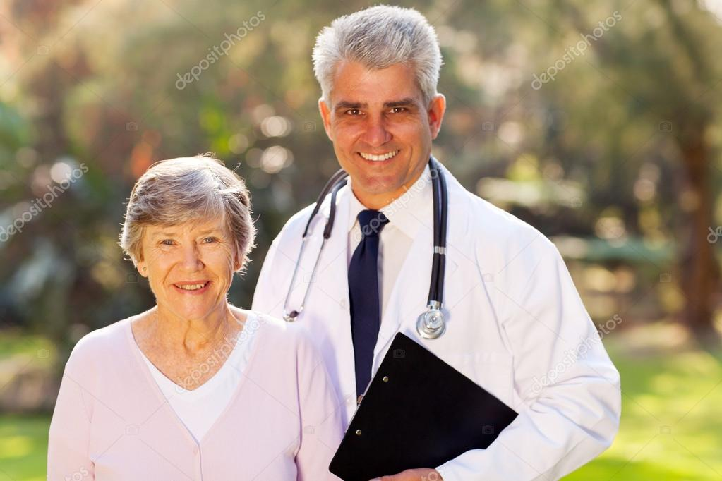 Middle aged doctor and senior patient outdoors