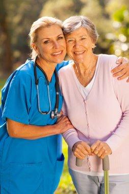 Caregiver hugging senior patient outdoors