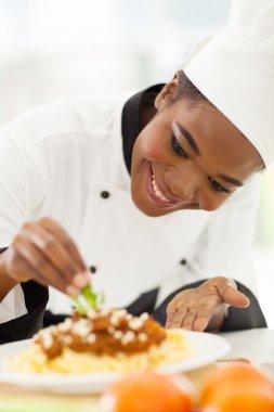 african american chef decorating pasta dish