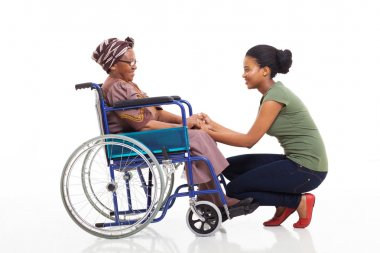 african daughter talking to disabled senior mother